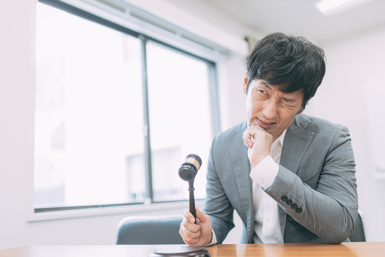 「直前まで入札に慎重な男性」の写真[モデル:大川竜弥]