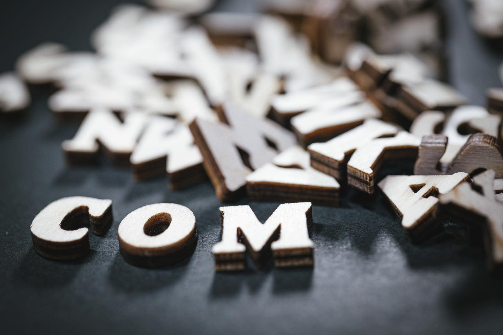 「散らばったアルファベットと.comドメイン」の写真