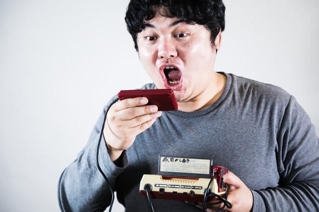 2IIコンのマイクで大声を発して仲間を呼ぶファミコン世代の写真