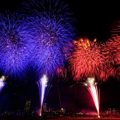 青と赤に別れて打ち上げる花火の写真
