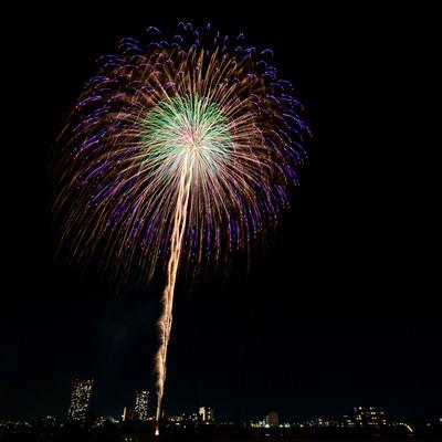 都心の夜空に打ち上がる花火の写真