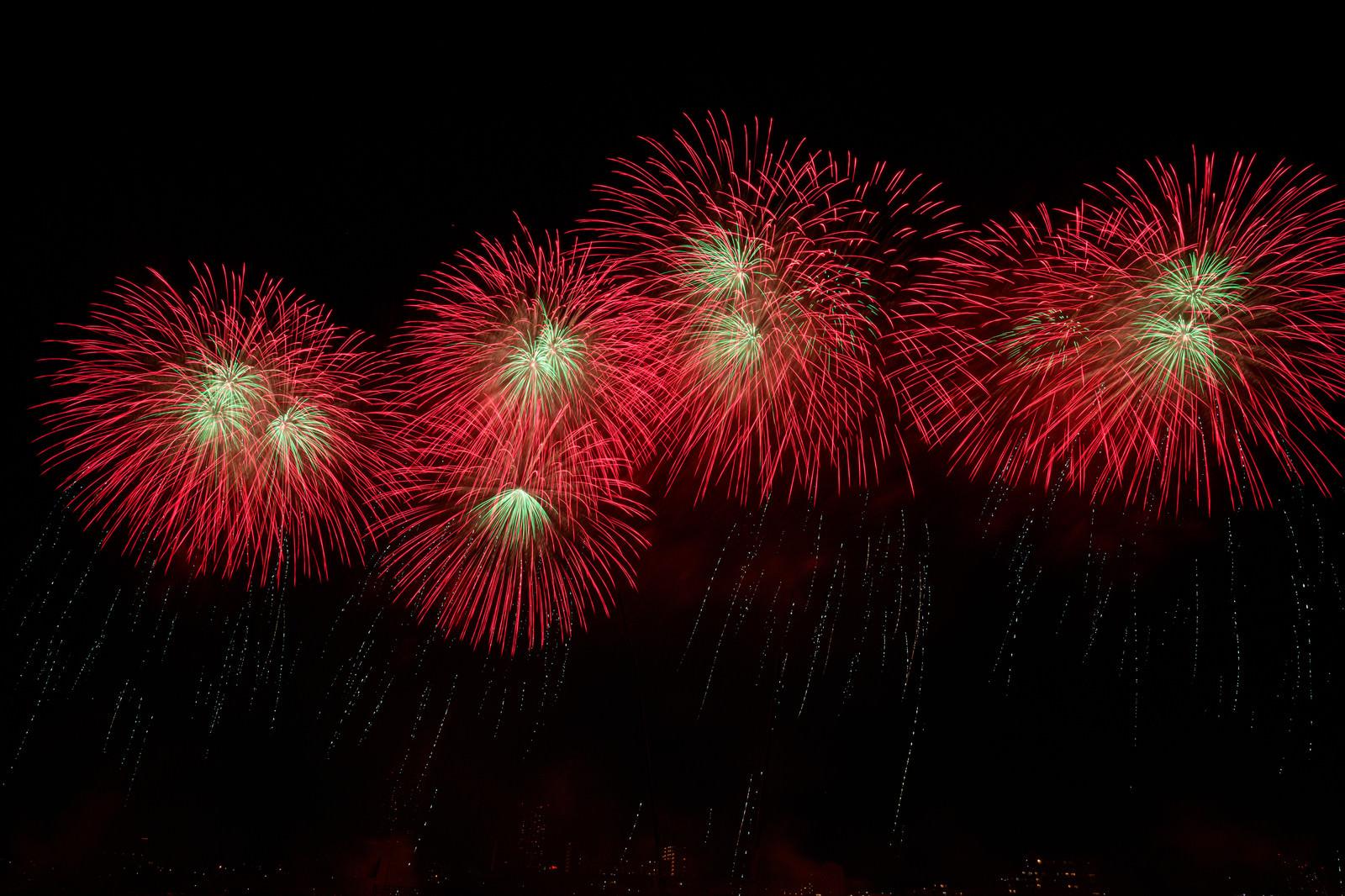「夜空に流れる赤い打上花火」の写真