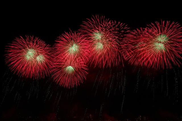夜空に流れる赤い打上花火の写真