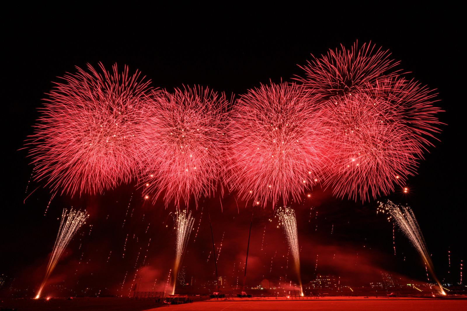 「赤い光が夜空を染める江戸川区花火大会のスターマイン」の写真
