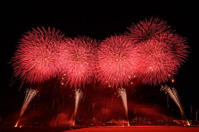 赤い光が夜空を染める江戸川区花火大会のスターマインの写真