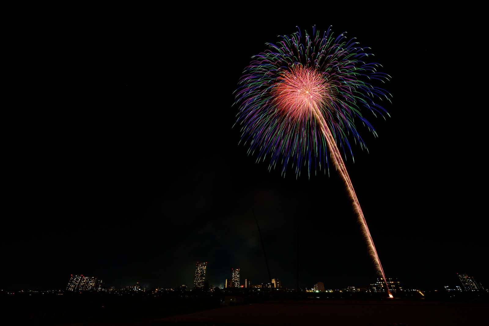 「都会の夜空に打ち上がる花火」の写真