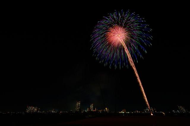 都会の夜空に打ち上がる花火の写真