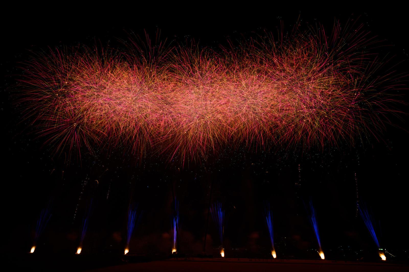 「夜空に炸裂する赤い打ち上げ花火」の写真