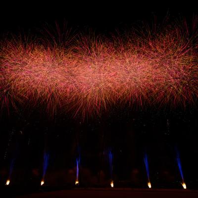 夜空に炸裂する赤い打ち上げ花火の写真