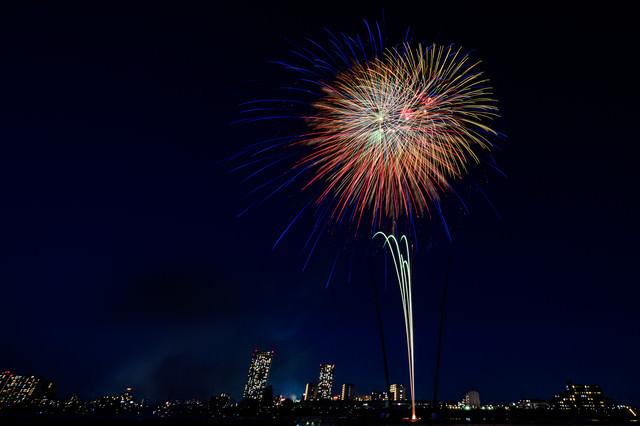 都会のビルと打上花火の写真