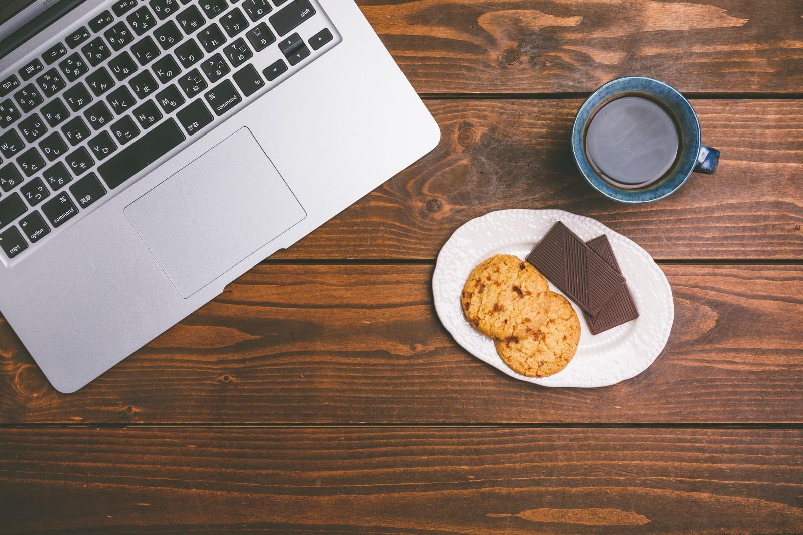「ノートパソコンで仕事したらコーヒーとお菓子でブレイクタイム」の写真