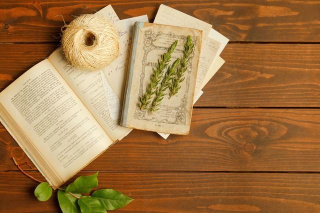 開かれた古書の上に置かれた紐と薬草