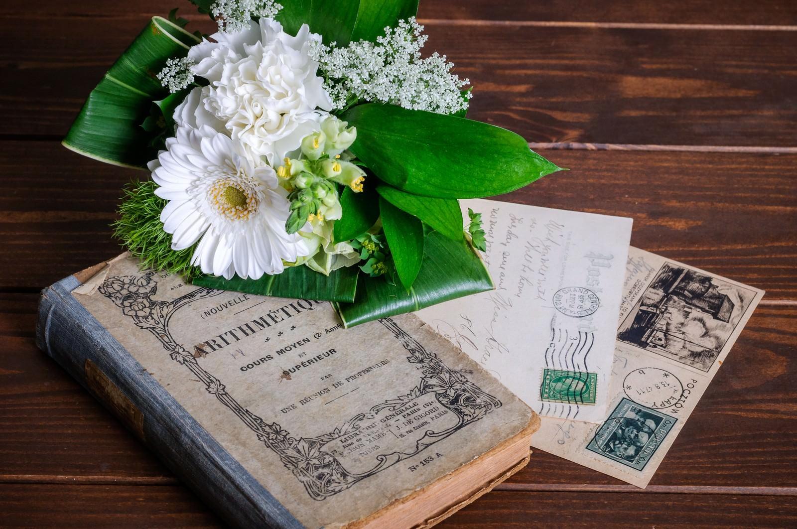 「無造作に置かれた洋書と葉書の上にあるブーケ」の写真