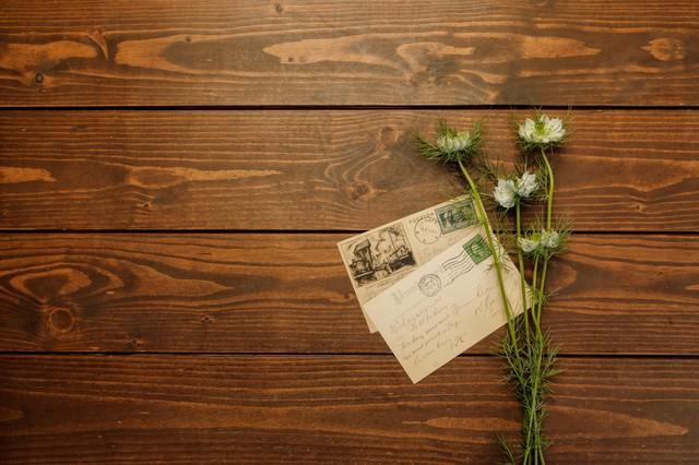 アンティークデスクに置かれた葉書と庭で摘んだ名もなき花の写真