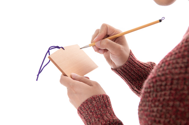 絵馬に願い事を書き込むの写真