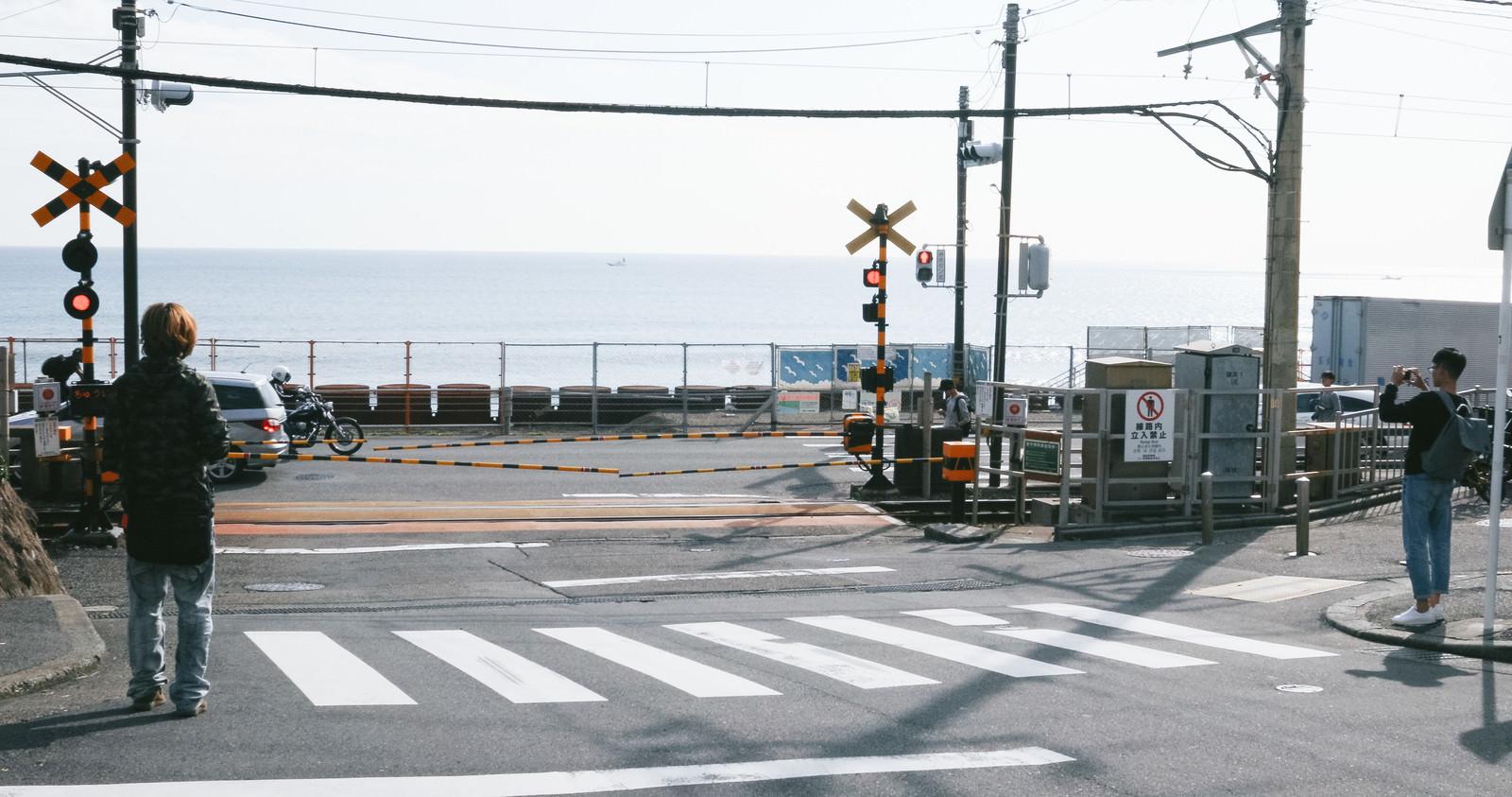 「【聖地巡礼】鎌倉高校前駅の踏切を撮影する台湾人観光客」の写真