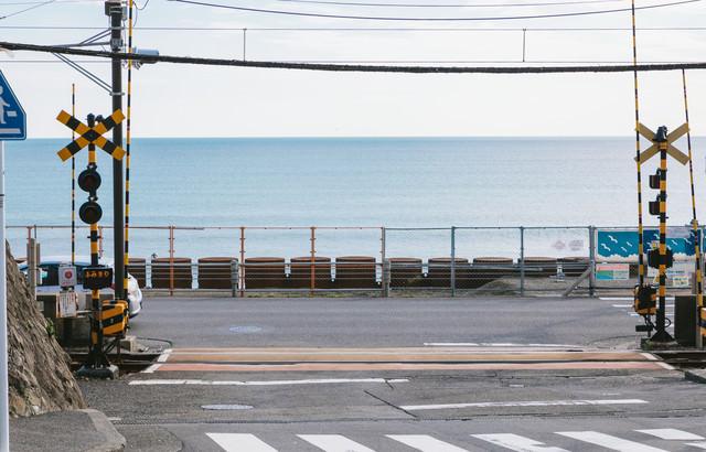 江ノ島の海が広がる鎌倉高校前駅の踏切の写真