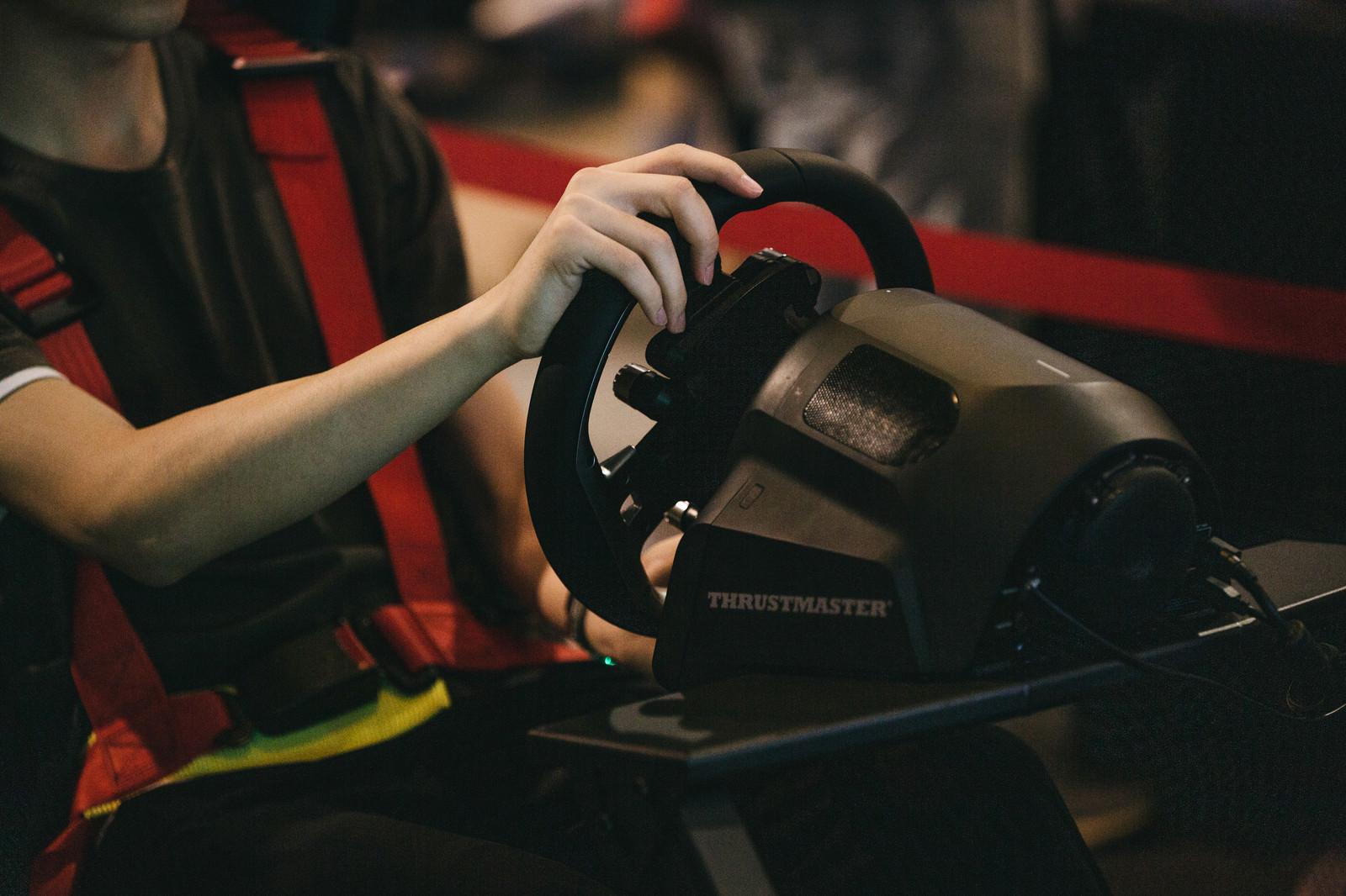 「eスポーツのレースゲームでハンドルを持って操作する」の写真