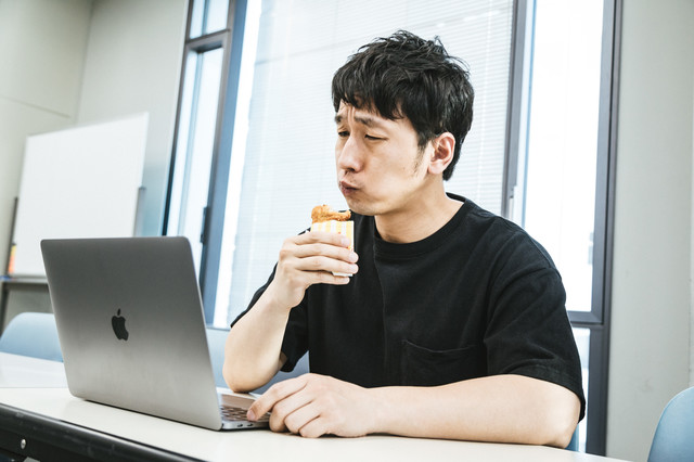 自分の動画を見ながらフライドチキンを食べるユーチューバーの写真