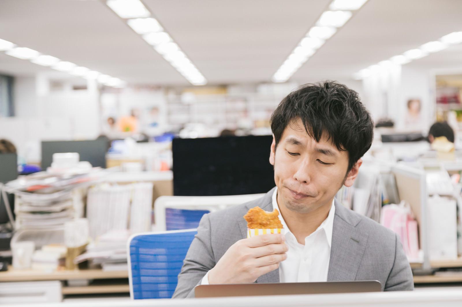 「仕事中に骨なしフライドチキンを食べるサラリーマン」の写真[モデル:大川竜弥]