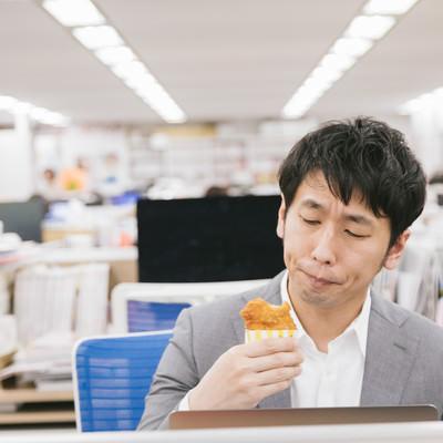 仕事中に骨なしフライドチキンを食べるサラリーマンの写真