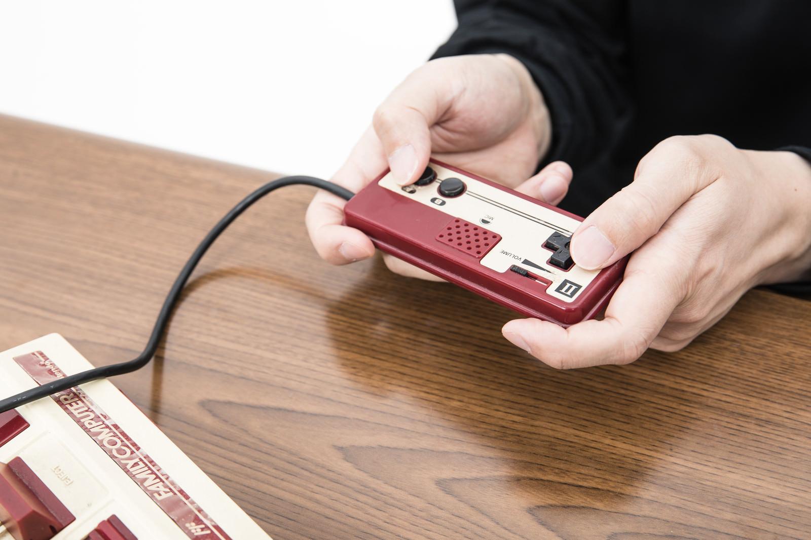 「2コンで遊ぶ男性の手元」の写真[モデル:大川竜弥]