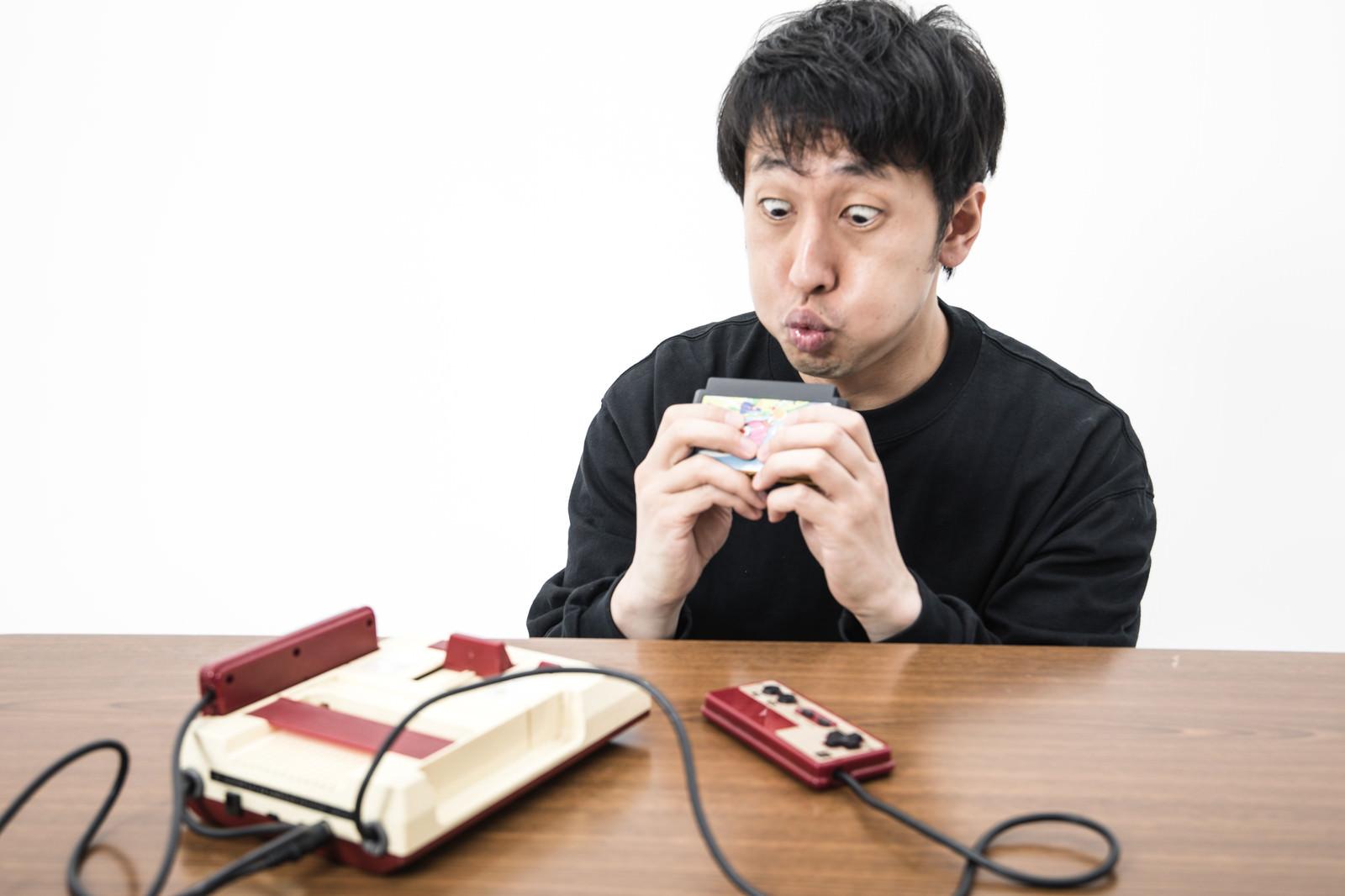 「カセットに息を吹きかけるゲーマー」の写真[モデル:大川竜弥]