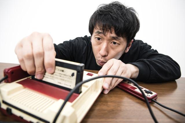 ゲーム機本体にカセットを差し込む男性の写真