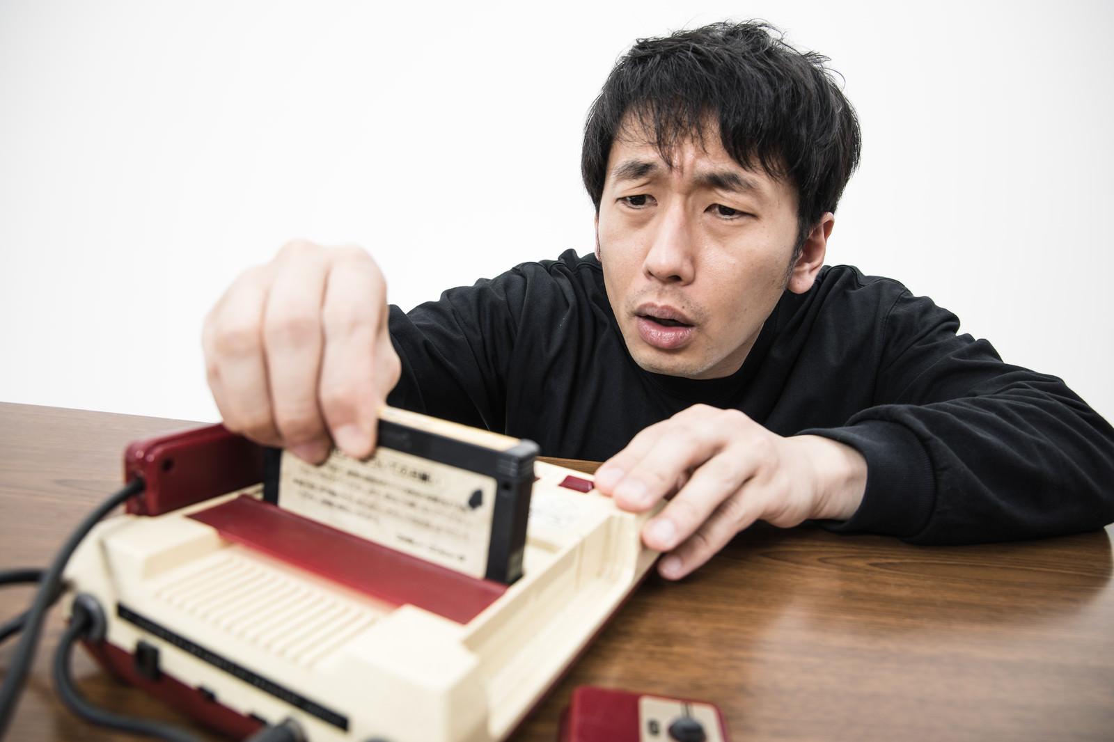「カセットの角度調整に苦戦するゲーマー」の写真[モデル:大川竜弥]