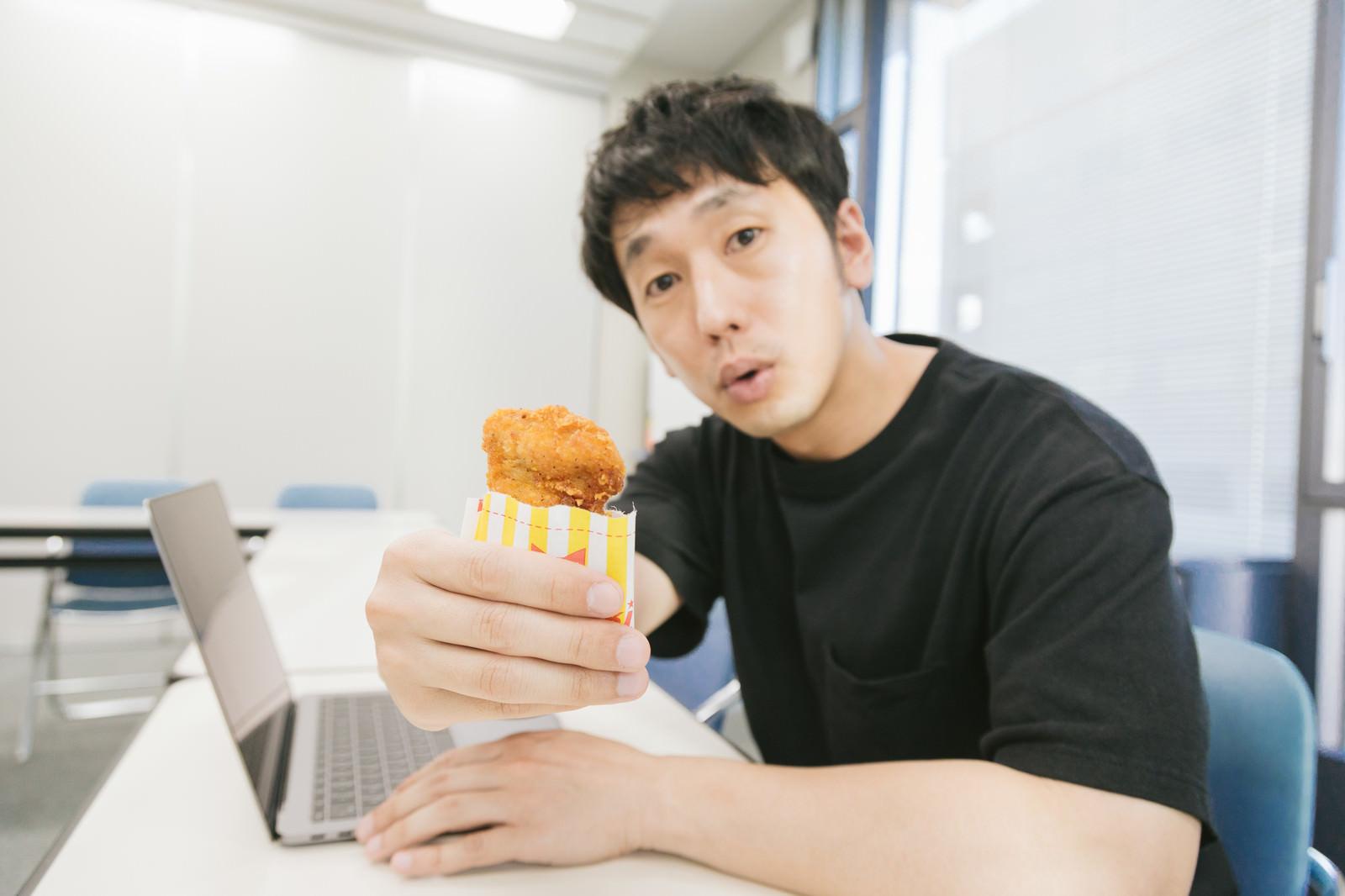 「フライドチキンをシェアする酉年の男性」の写真[モデル:大川竜弥]