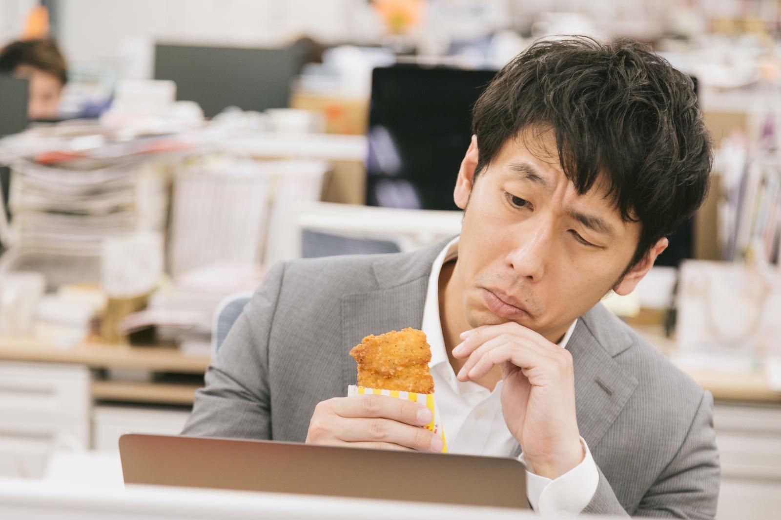 「「仕事中に食べたら怒られるかな?」と悩むチキン野郎」の写真[モデル:大川竜弥]