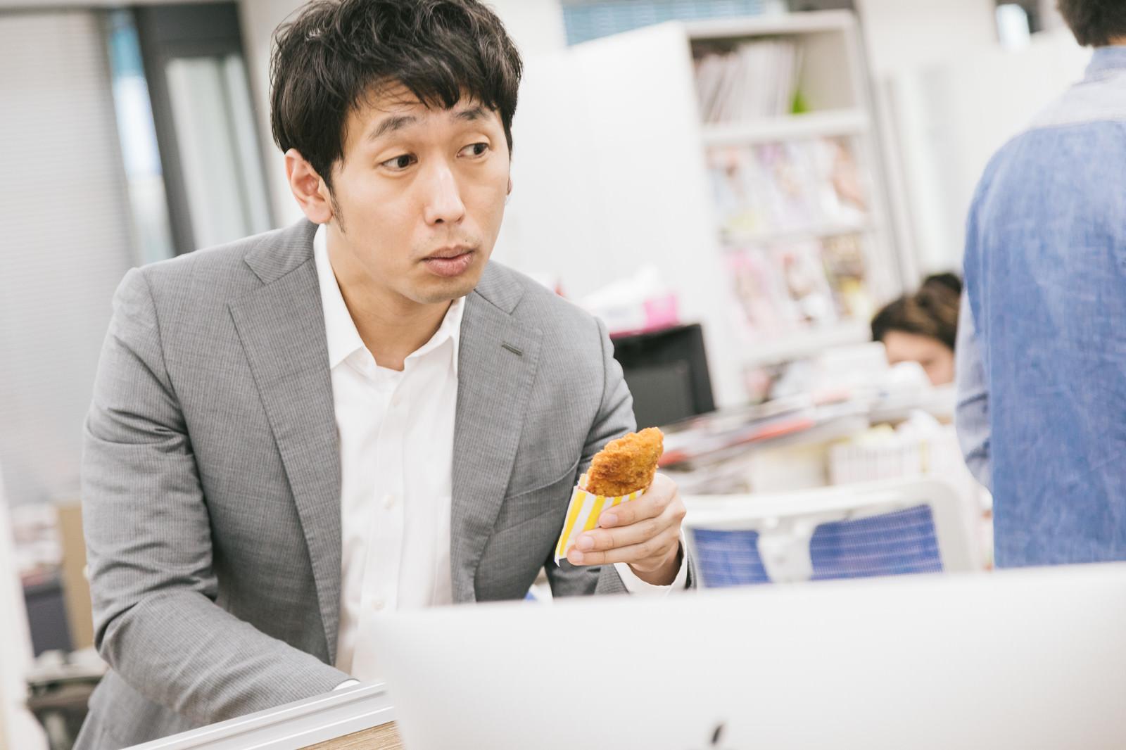 「「フライドチキン食べる?」と勧める隣席の先輩「フライドチキン食べる?」と勧める隣席の先輩」[モデル:大川竜弥]のフリー写真素材を拡大
