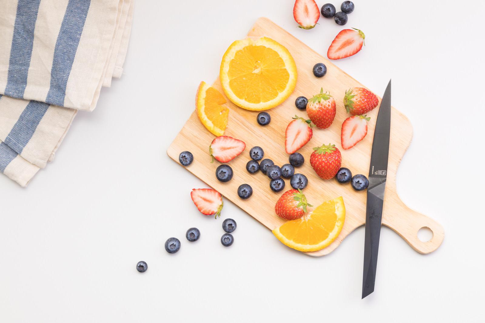「まな板に置かれたままのカット中のフルーツ」の写真