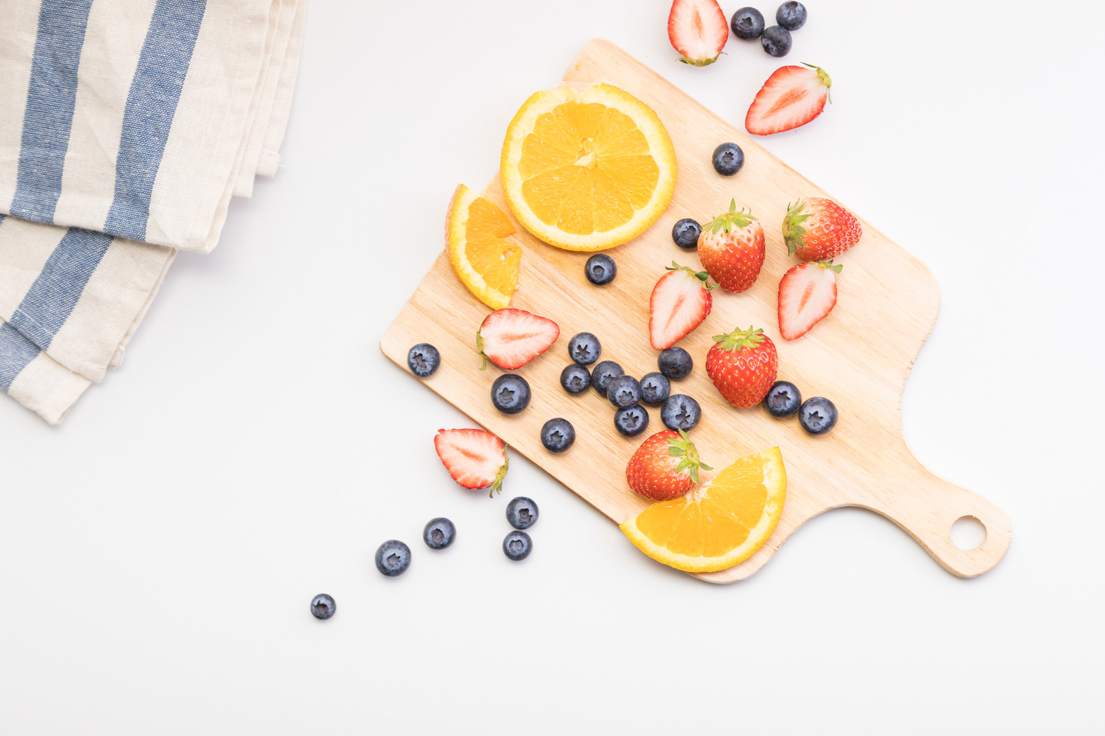 「まな板に散らばったカットフルーツ」の写真