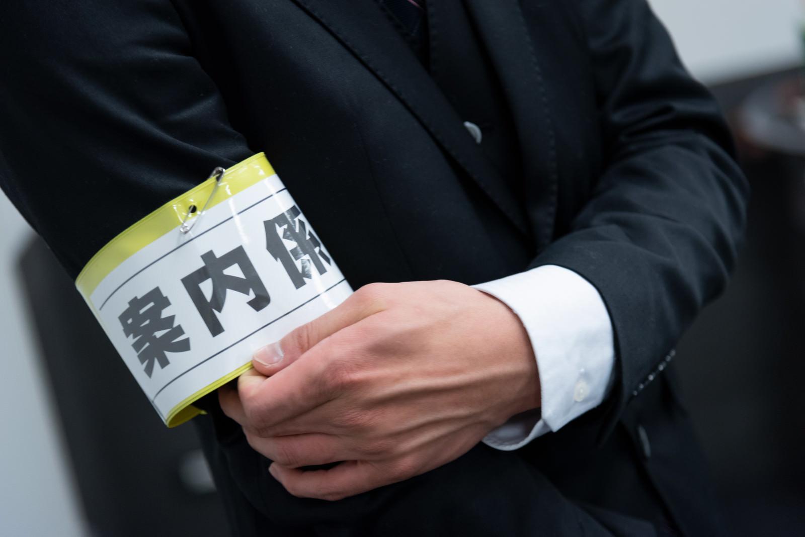 「案内係の腕章」の写真[モデル:村田裕章]