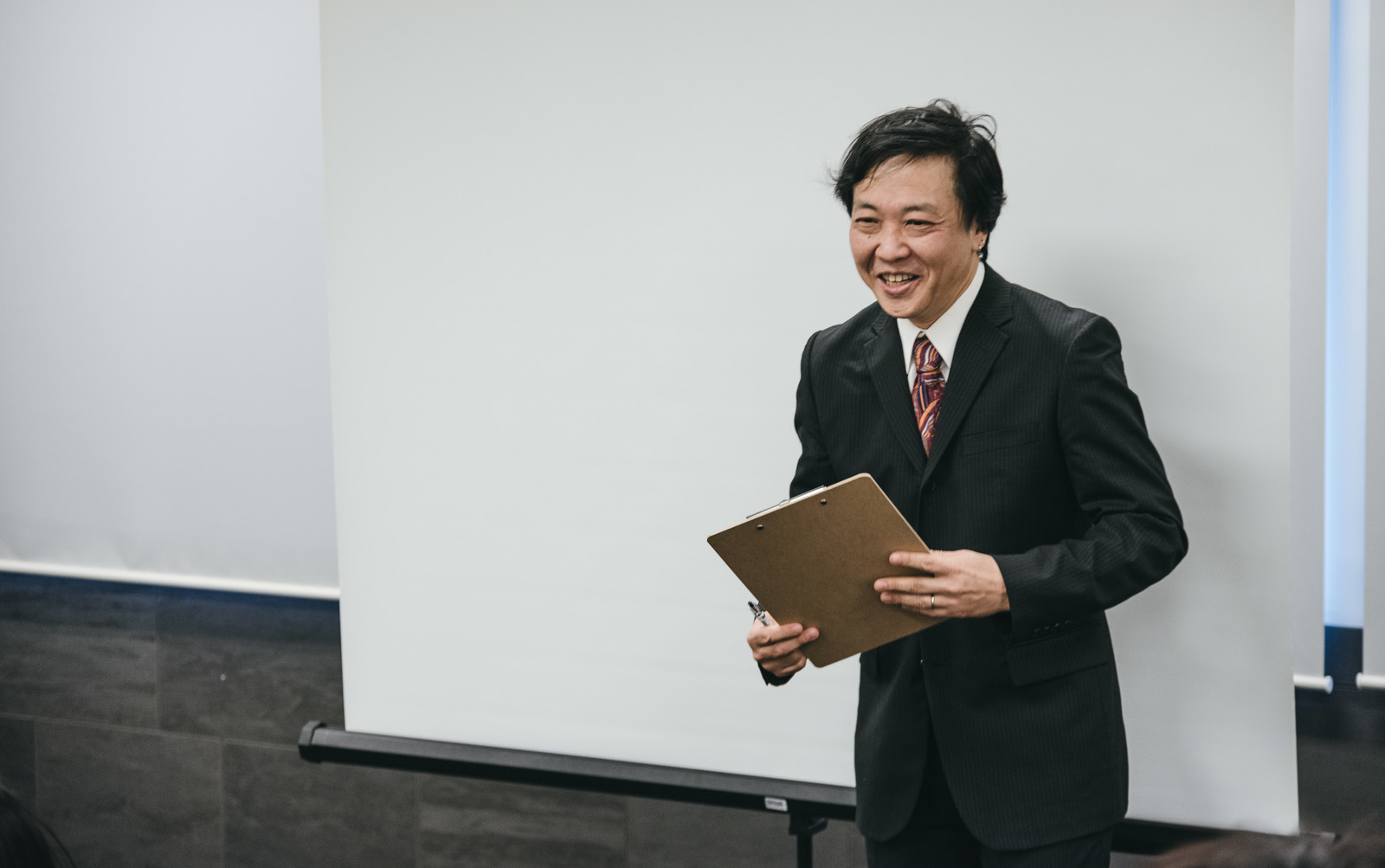 「笑顔でセミナー参加者と対話する塾長」の写真[モデル:のせさん]