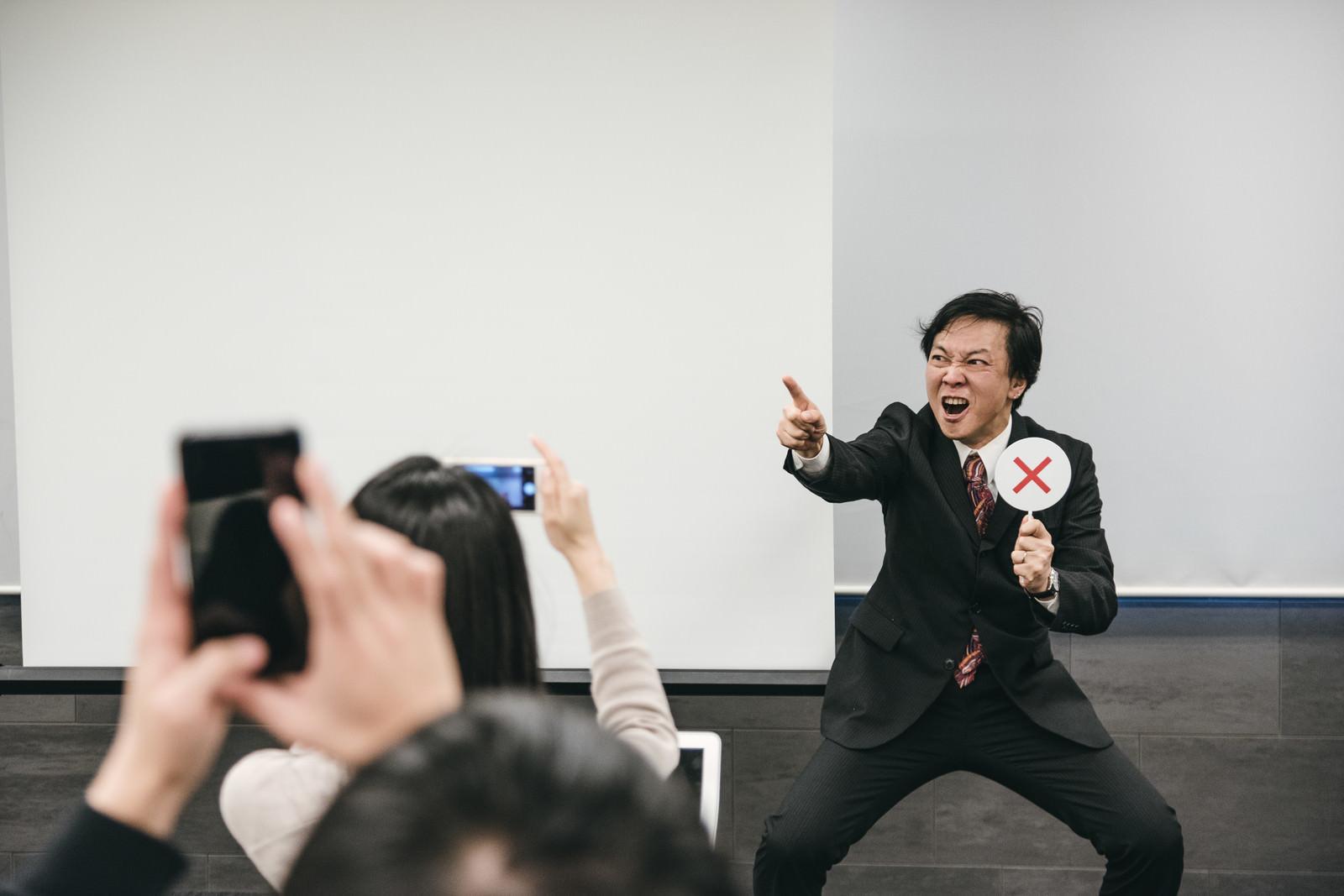 「荒ぶった講師を撮影する参加者」の写真[モデル:のせさん]