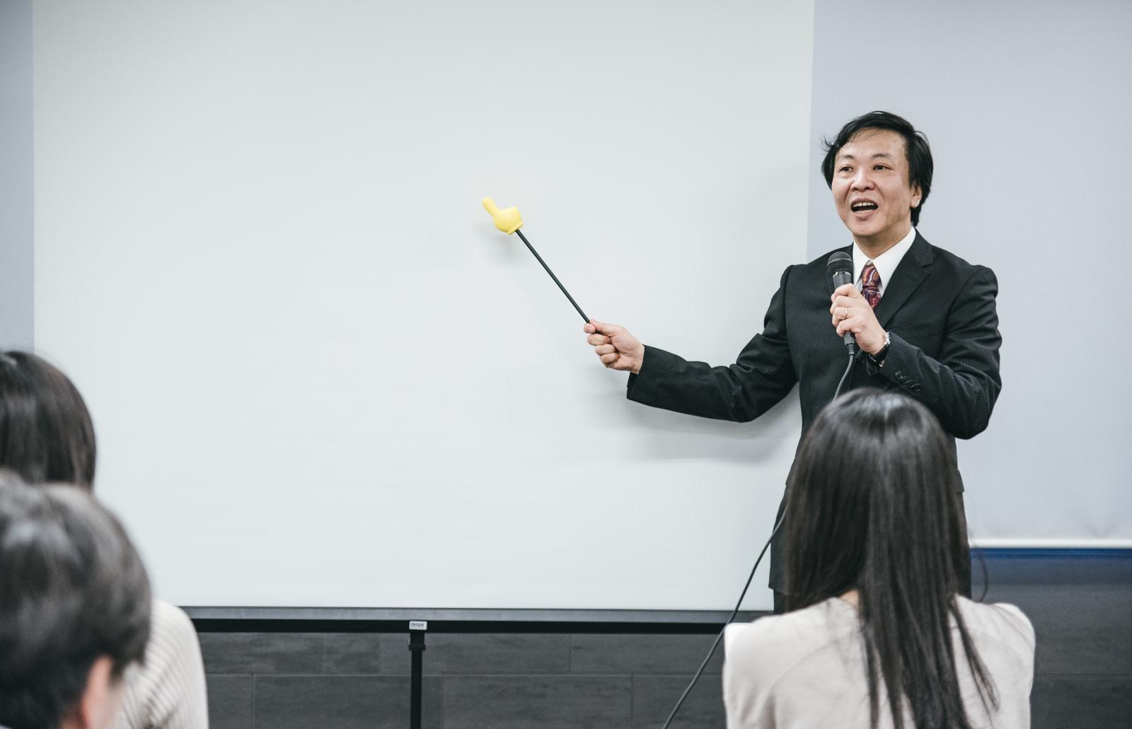 「ホワイトボードを見ながら登壇するセミナー講師」の写真[モデル:のせさん]
