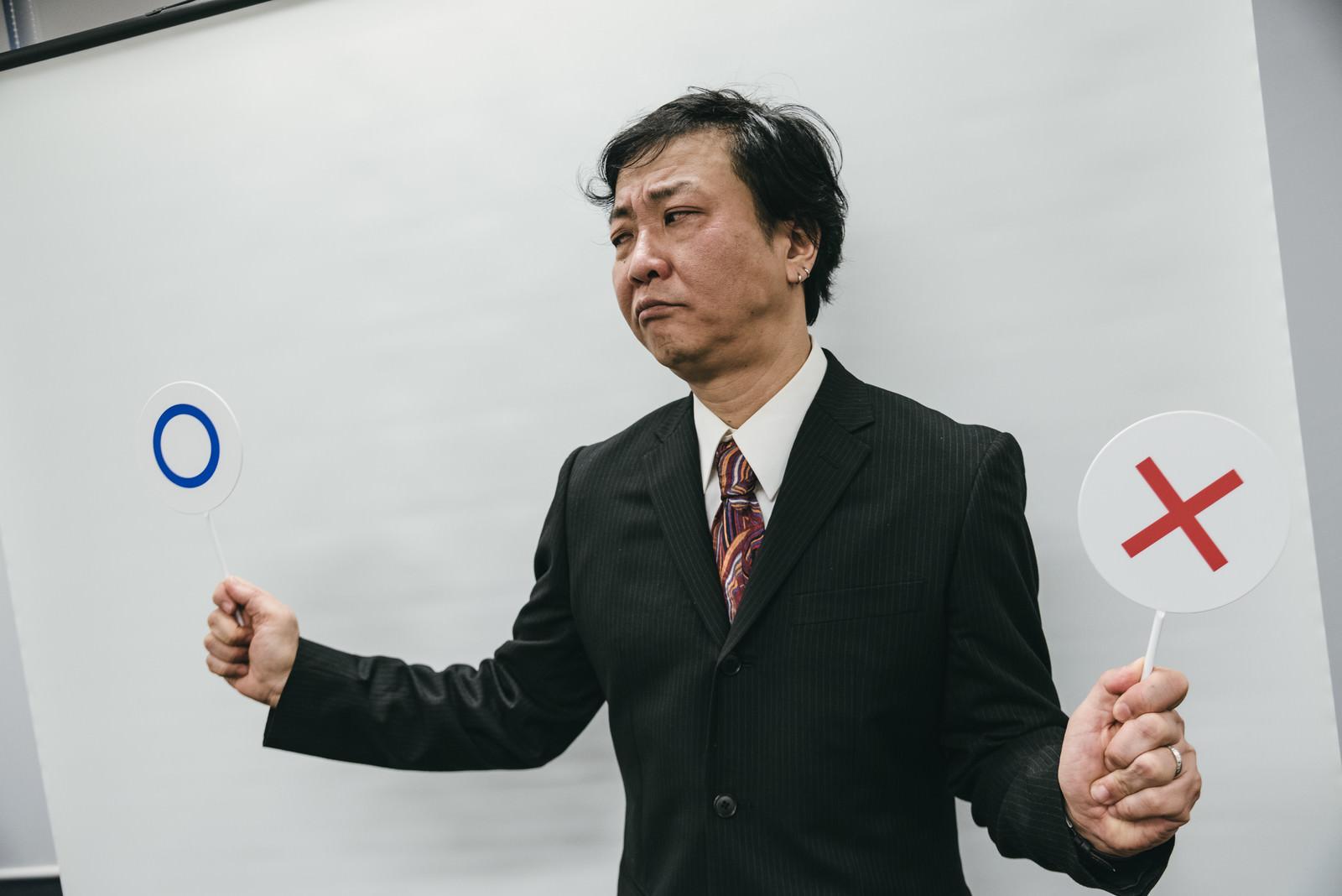 「○×クイズで難儀する上司」の写真[モデル:のせさん]