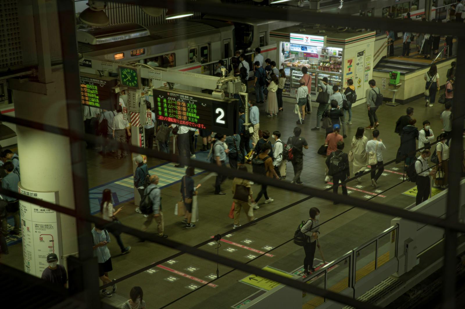 「駅のホームで往来する人」の写真