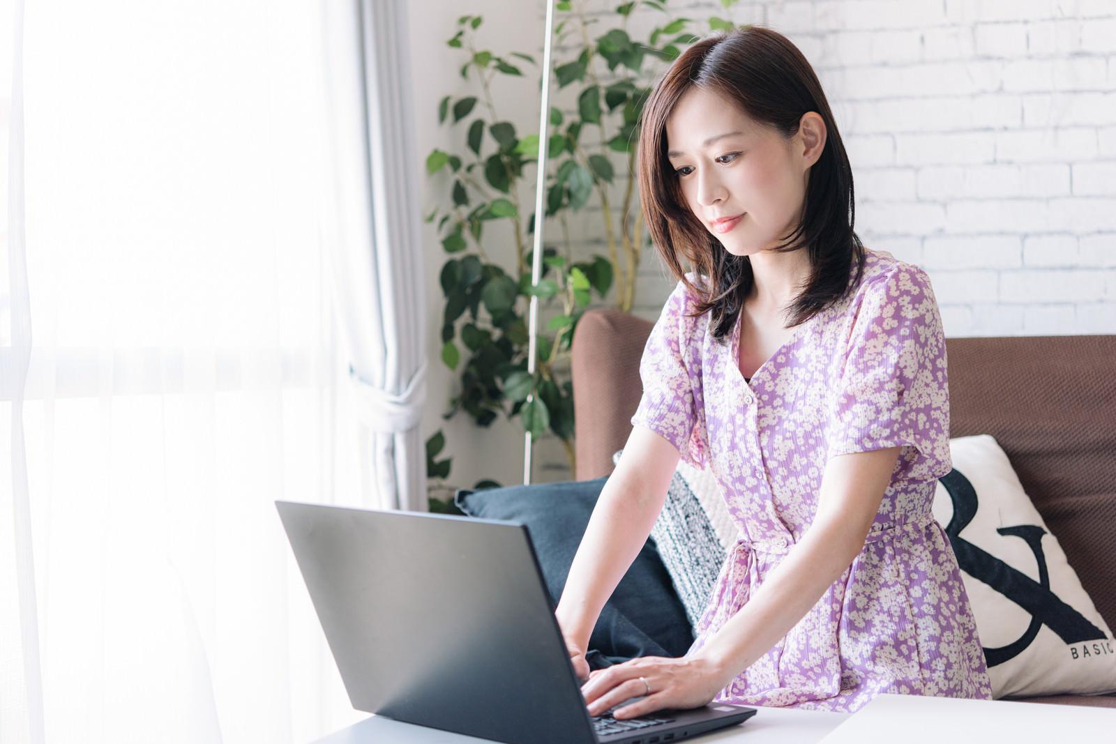 「自宅のノートパソコンでリモートワークする女性」の写真