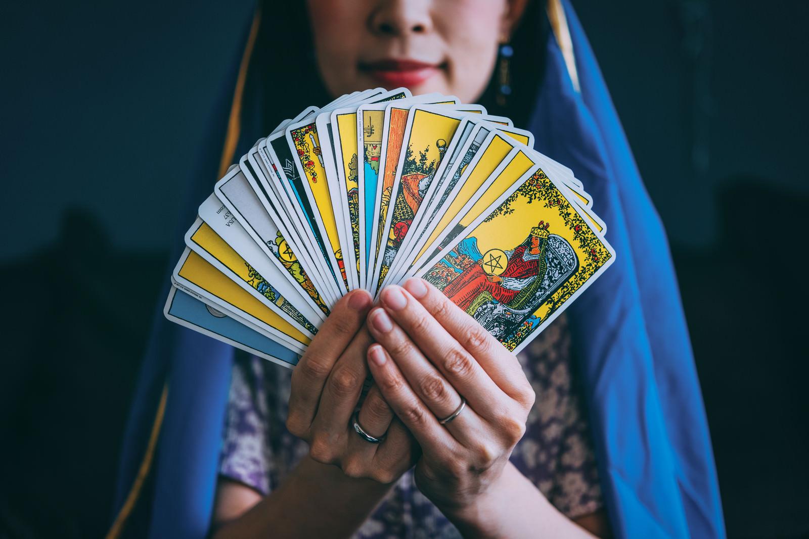 「タロットカードを扇状に見せる占い師」の写真