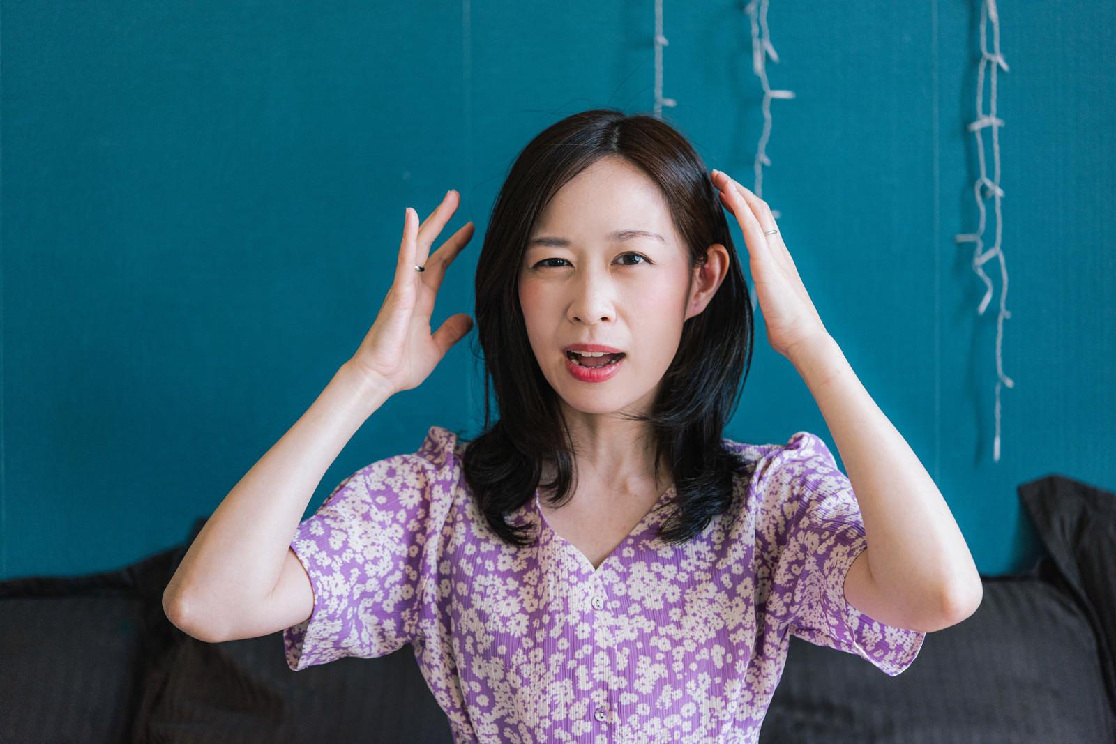 「失敗して頭を抱える女性」の写真