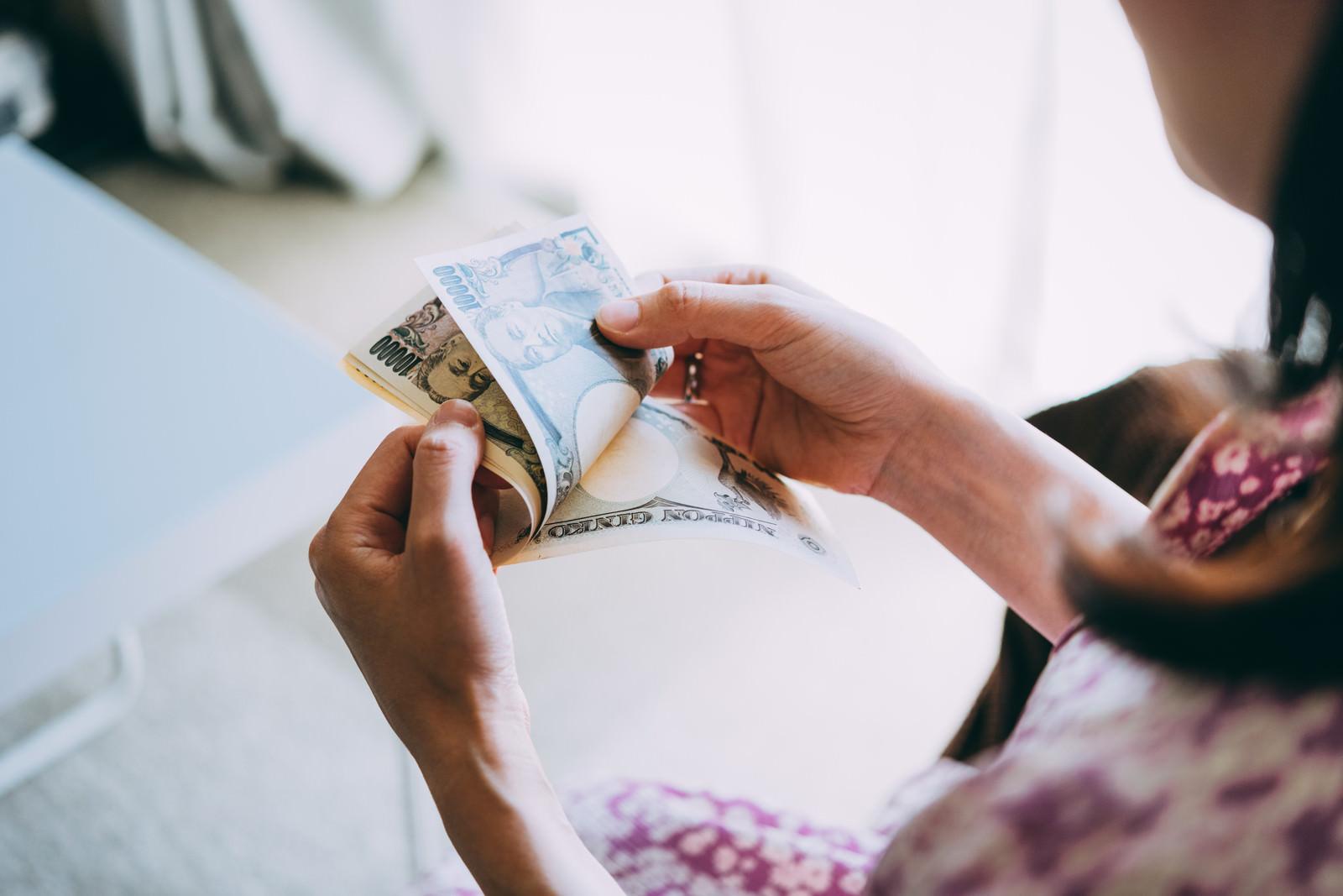 「在宅ワークの副業で得た報酬を数える女性の手元」の写真