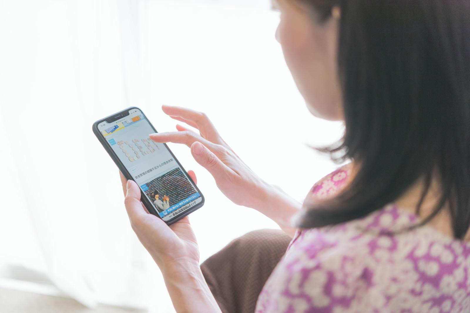 「スマホで副業関連のニュースをチェックする女性」の写真