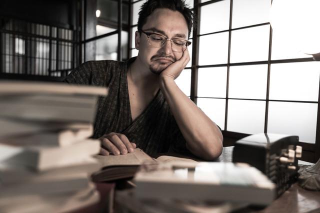 文豪の真似をしながら書籍を読む外国人の写真