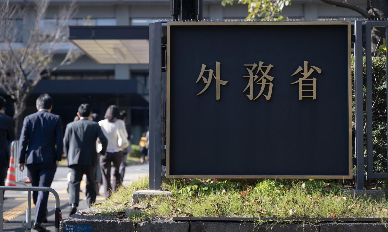 「外務省に出入りする職員の後ろ姿」の写真