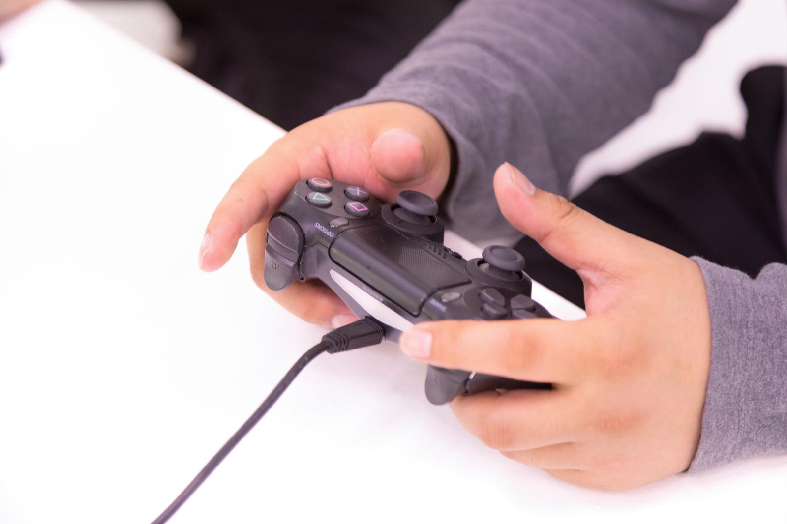 「コントローラーでプレイする男性の手元」の写真[モデル:段田隼人]