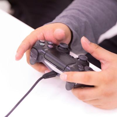 コントローラーでプレイする男性の手元の写真
