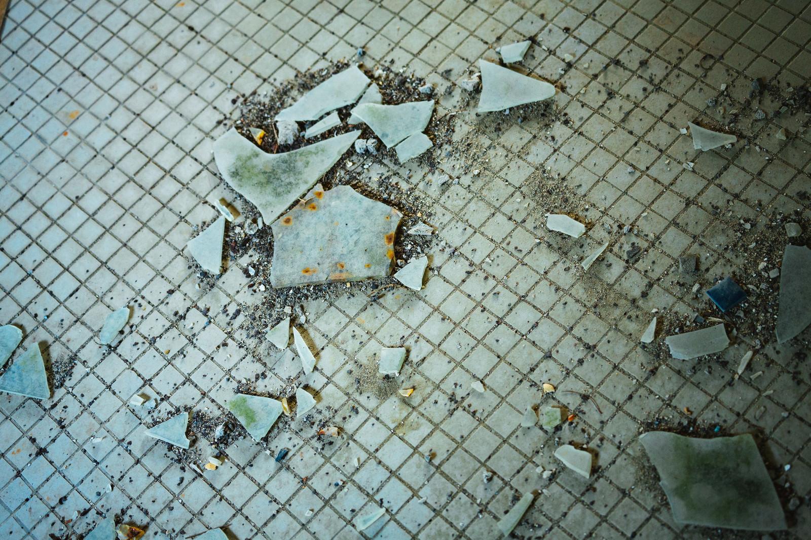 「汚れたタイルと飛び散るガラス片」の写真